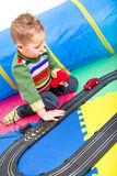 Boy playing with Racetracks Stock Photo