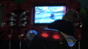 Boy playing racing game on bike simulator. MOSCOW, RUSSIA - SEPTEMBER 10, 2016: Child playing racing game riding simulator bike, focus on blinking backlights stock video footage