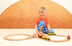 Boy playing with railroad toy Stock Photos
