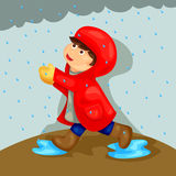 Boy playing in the rain Stock Image