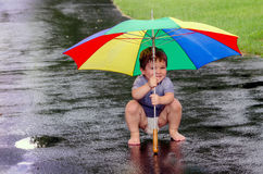 Boy playing in the rain with umbrella stock photos