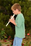 Boy playing a recorder Royalty Free Stock Image