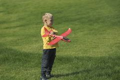 Boy playing with a red airplane royalty free stock image