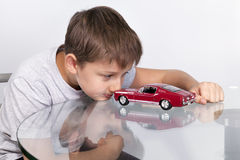 Boy playing with red sports car on a glass table Stock Photo