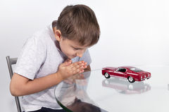 Boy playing with red sports car on a glass table Royalty Free Stock Image