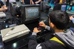Boy playing with retro Atari Pac Man at Games Week 2015 Royalty Free Stock Image