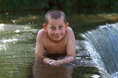 Boy playing in the river Stock Image