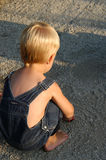Boy Playing in the Rocks. A little boy stopping to play with some pebbles in the path Stock Photo