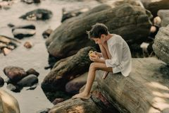 The boy is playing on rocks stock photography