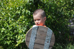 Boy playing role of young warrior. With buckler Stock Photo