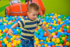 A boy in the playing room with many little colored balls Royalty Free Stock Photos