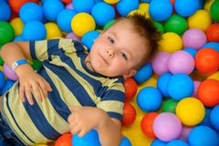 A boy in the playing room with many little colored balls Stock Photography