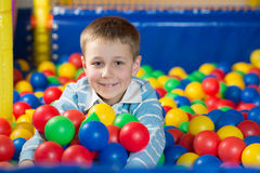 A boy in the playing room with many little colored balls Stock Photos
