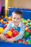 A boy in the playing room with many little colored balls Royalty Free Stock Photography