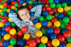 A boy in the playing room with many little colored balls Royalty Free Stock Photo