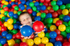 A boy in the playing room with many little colored balls Stock Image