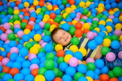 A boy in the playing room with many little colored balls Stock Images