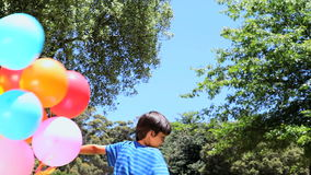 Boy playing with rubber balloon in a park stock video