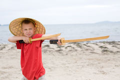 Boy playing with samurai swords made Royalty Free Stock Image