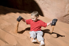 Boy playing in sand. A young boy dumping red sand out of his shoes Royalty Free Stock Image