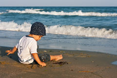 Boy playing with sand Stock Image