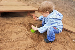 Boy playing with sand. Boy playing in sand-box, collect sand in bucket and clap Royalty Free Stock Photo
