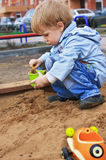 Boy playing with sand. Boy playing in sand-box, collect sand in bucket Stock Image