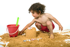 Boy playing in the sand. Isolated on white stock images