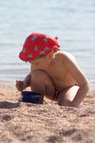 Boy playing in sand. Young boy wearing a hat and swimsuit playing on a sandy beach by the water Royalty Free Stock Images