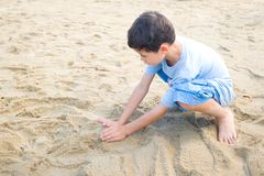 Boy playing with sand at the beach Royalty Free Stock Images