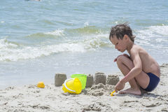 Boy playing with sand on the beach, building towers, Stock Image