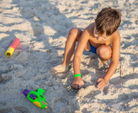 Boy playing with sand in the beach Stock Photography