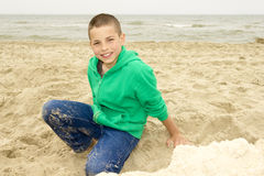 Boy playing in sand on beach, Northern Sea coast Stock Images