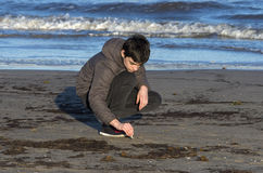 Boy playing with sand on the beach royalty free stock photography