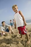 Boy Playing in Sand with Family at Beach Stock Images