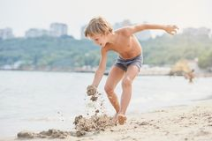 Boy playing with sand stock photo