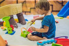 Boy playing with sand in preschool. The development of fine motor concept. Creativity Game concept stock photography