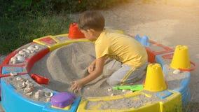 Boy playing with sand in a sandbox. Cute boy playing with sand in a sandbox stock footage