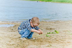 Boy playing in the sand on shore of Lake Stock Photos