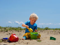Boy playing in the sand with shovel and bucket Stock Photo