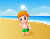 Boy playing a sand using his feet at the beach Stock Photo