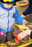 Boy Playing in Sandbox. Little boy playing in the sandbox with mother Stock Image