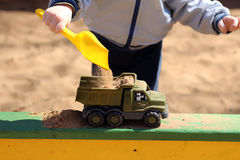 Boy playing in sandbox. Sand and toys Stock Photos