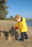 Boy playing with Sandcastle. Toddler (3) playing with water and a sand castle on a beach in autumn Stock Photography