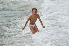 Boy playing at the sea Stock Images