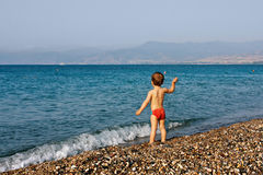 Boy playing on sea beach Stock Photos