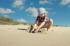 A boy playing on the sea beach. The boy builds a sandcastle at the beach Stock Photography