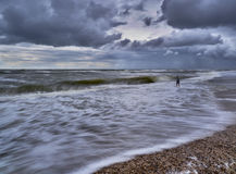 Boy playing in the sea. A boy plays in the sea on a stormy autumn day in Denmark Royalty Free Stock Image