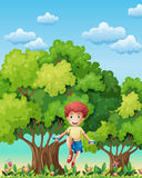 A boy playing with the skipping rope near the trees Stock Images