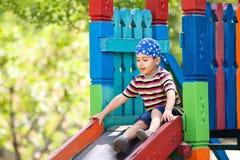 Boy  playing on slide Stock Photo